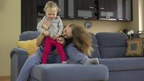 Le beau chatouillement de femme font ses premiers pas l'estomac d'enfant se reposant sur le sofa clips vidéos