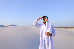 Le beau cheik d'émirat regarde dans la caravane de distance des chameaux Image libre de droits