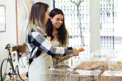 Le beau client de jeune femme choisissant des spaghetti s'est vendu en poids dans la boutique organique Image libre de droits