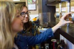Le beau client de jeune femme choisissant le thé s'est vendu en poids dans la boutique organique photo libre de droits