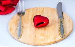 Le beau coeur de jouet se trouve sur un hachoir Image libre de droits