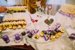 Le beau coeur sur le bâton est placé dans le petit gâteau La table de mariage de dessert Photographie stock libre de droits