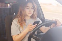 Le beau conducteur femelle tient le téléphone intelligent, les types message textuel au téléphone intelligent tandis que les supp photo stock
