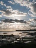 Le beau coucher du soleil au-dessus de la baie de mer de côte de port opacifie la silhouette de Photos libres de droits
