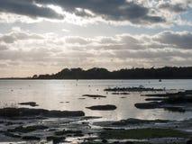 Le beau coucher du soleil au-dessus de la baie de mer de côte de port opacifie la silhouette de Photo stock