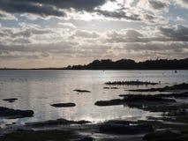 Le beau coucher du soleil au-dessus de la baie de mer de côte de port opacifie la silhouette de Image stock
