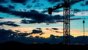 Le beau coucher du soleil avec le soleil rayonne au-dessus de la ville avec une silhouette de grue banque de vidéos