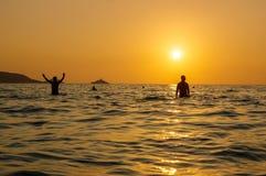Le beau coucher du soleil romantique scénique au-dessus de la mer avec la silhouette de personnes dans la position dans l'eau et  Photo stock