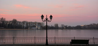 Le beau coucher du soleil rose réfléchissent sur le lac couvert de la glace image libre de droits