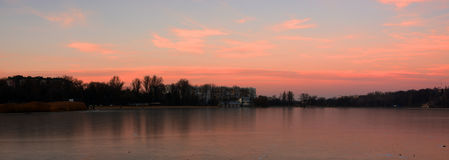 Le beau coucher du soleil rose réfléchissent sur le lac couvert de la glace photo libre de droits