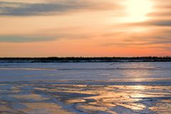 Le beau coucher du soleil sur le ciel bleu-foncé de soirée a réfléchi sur la glace de rivière, Photos libres de droits
