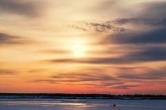 Le beau coucher du soleil sur le ciel bleu-foncé de soirée a réfléchi sur la glace de rivière, Images libres de droits