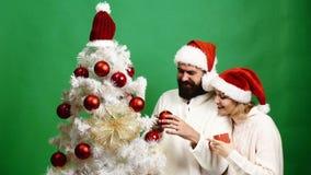 Le beau couple décore l'arbre de Noël sur le fond vert Concept de la célébration de la nouvelle année banque de vidéos