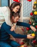 Le beau couple décore un arbre de Noël Photos stock