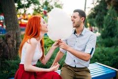 Le beau couple d'amour mange la sucrerie de coton sur un banc Photos stock
