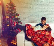 Le beau couple dans l'amour se trouve sur un divan enveloppé dans le plaid le Christ Photo stock