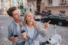 Le beau couple se repose ensemble sur l'anf de moto regardant l'un l'autre Ils tiennent des tasses de café dans des mains Photo stock