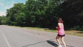 Le beau coureur féminin folâtre dans les écouteurs et la chemise rose s'exerce en parc de ville La femme caucasienne de brune min banque de vidéos