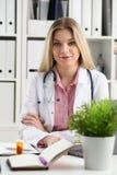 Le beau docteur féminin de sourire s'asseyent sur le lieu de travail Photos libres de droits