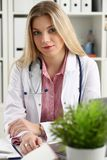 Le beau docteur féminin de sourire s'asseyent sur le lieu de travail Images stock