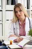 Le beau docteur féminin de sourire s'asseyent sur le lieu de travail Photographie stock