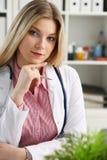Le beau docteur féminin de sourire s'asseyent sur le lieu de travail Photographie stock libre de droits