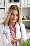 Le beau docteur féminin de sourire s'asseyent sur le lieu de travail Photo stock