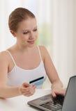 Le beau femme avec l'ordinateur portatif effectue le paiement en ligne Photos libres de droits