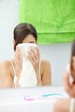 Le beau femme essuie son visage avec un essuie-main Photo stock
