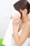 Le beau femme essuie son visage avec un essuie-main Image stock