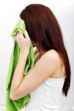 Le beau femme essuie son visage avec un essuie-main Images stock