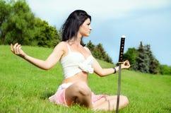 Le beau femme médite sur la pelouse verte photo stock
