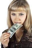 Le beau femme mord cents billets de banque du dollar Photos stock