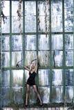 Le beau femme reste près du mur en verre Image libre de droits