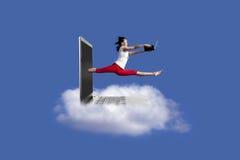 Le beau femme saute avec l'ordinateur portatif Image stock