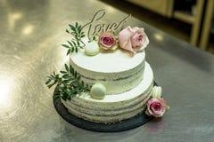 Le beau gâteau de mariage avec de la crème avec amour des textes sur le rose supérieur fleurit des roses Photos libres de droits