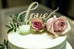 Le beau gâteau de mariage avec de la crème avec amour des textes sur le rose supérieur fleurit des roses Image stock