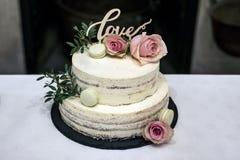Le beau gâteau de mariage avec de la crème avec amour des textes sur le rose supérieur fleurit des roses Photo stock