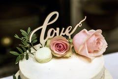 Le beau gâteau de mariage avec de la crème avec amour des textes sur le rose supérieur fleurit des roses Image libre de droits