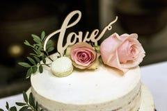 Le beau gâteau de mariage avec de la crème avec amour des textes sur le rose supérieur fleurit des roses Images stock