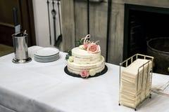 Le beau gâteau de mariage avec de la crème avec amour des textes sur le rose supérieur fleurit des roses Photo libre de droits