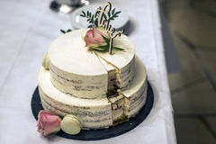 Le beau gâteau de mariage avec de la crème avec amour des textes sur le rose supérieur fleurit des roses Images libres de droits
