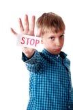 Le beau garçon blond dans une chemise bleue montre un arrêt de message semblant triste Images libres de droits