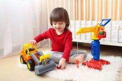 Le beau garçon d'enfant en bas âge joue des voitures à la maison Images libres de droits