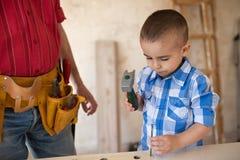 Le beau garçon frappe un clou avec un marteau Photographie stock libre de droits