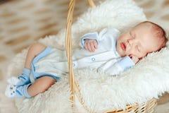 Le beau garçon nouveau-né de sommeil est habillé dans des combinaisons et les butins se situe dans le panier Photo stock
