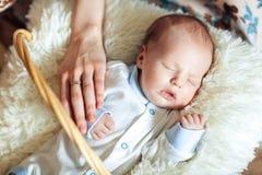 Le beau garçon nouveau-né de sommeil est habillé dans des combinaisons et les butins se situe dans le panier Photos stock