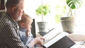 Le beau grand-père montre à son petit-fils son album de famille Valeur familiale clips vidéos