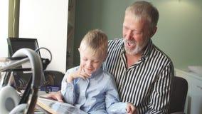 Le beau grand-père montre à son petit-fils son album de famille Valeur familiale banque de vidéos