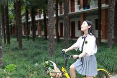 Le beau jaune adorable mignon heureux chinois asiatique de tour d'étudiant a partagé la bicyclette à l'école avant que son regard photos libres de droits